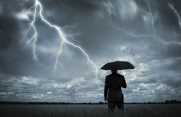 A businessman holding an umbrella in a storm.