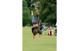 Boy standing upside down on his hands, on a Summer day, in a park surrounding the Berlin Reichstag