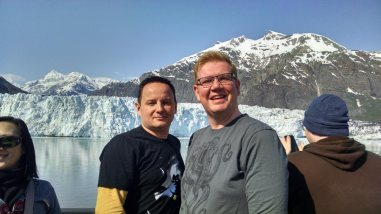On an Alaskan cruise, Nick & Greg of Roguetrippers pose in front of the beautiful glaciers and fjords of the inside passage in May 2015.