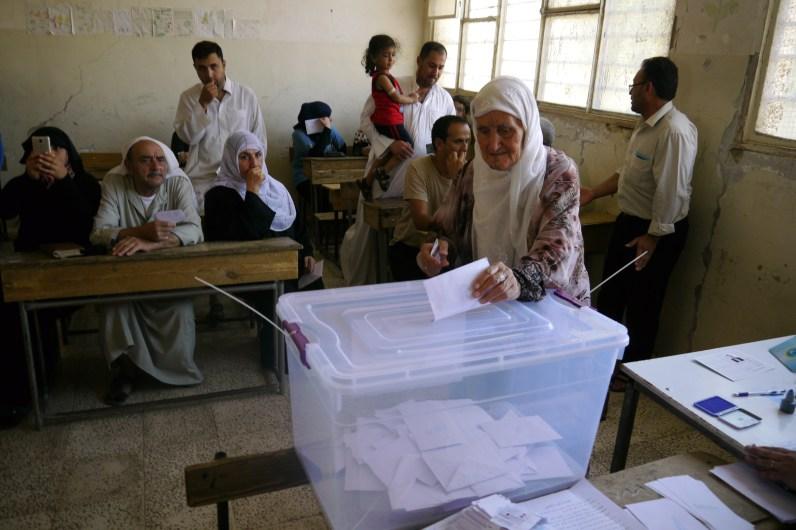 Una mujer vota en las elecciones comunales de rojava