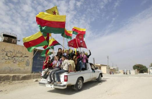 File photo shows people waving red, green and yellow Kurdish flags in the back of a truck as they celebrate what they said was the liberation of villages from Islamist rebels near the city of Ras al-Ain
