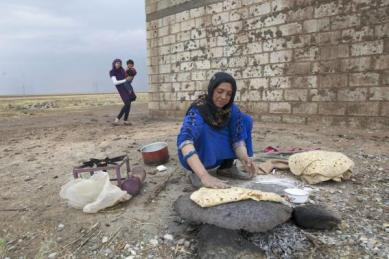 File photo shows a woman making bread near Al-Yaroubia crossing in the province of Hassaka