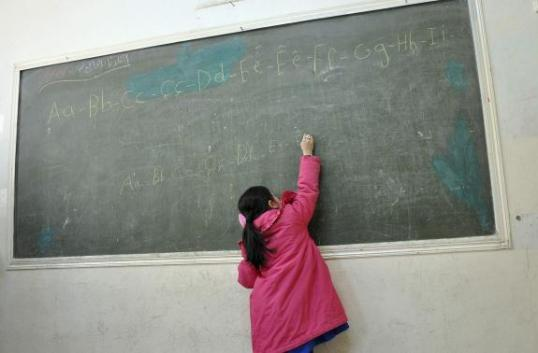 A Kurdish student writes on a board in a classroom in the town of Rumeilan