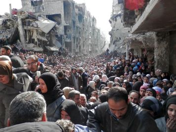 """This is the Yarmouk refugee camp, which houses Palestinians, in Damascus. It's been described as a """"living hell"""" and """"the worst place on Earth,"""" as a result of the utterly miserable living conditions. This 2014 photo, which shows masses of people waiting for food and aid amidst bombed-out buildings, is a perfect encapsulation of how bad things have gotten in Syria. (United Nation Relief and Works Agency/Getty Images)"""