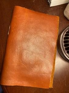 Distressed whiskey colored leather journal covering cream paper.