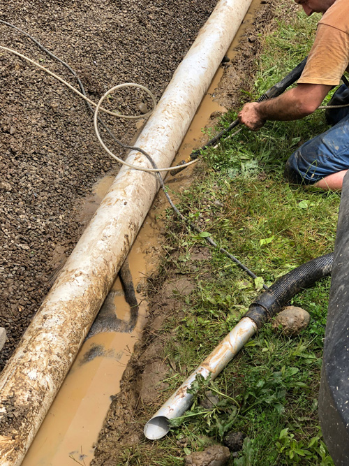 Worker using Roll-n-Vac to level pipe