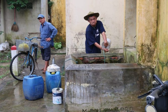 Man-collecting-water-from-well