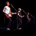 Dire Straits performing in Drammenshallen, Norway in 1985 (from left to right: John Illsley, Mark Knopfler, Jack Sonni). Photo: Helge Øverås/Wikimedia Commons