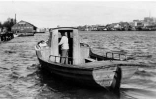 Dette bildet av fergemann Bjørvin Hansen (f. 1911) ved Hauge fergested er tatt på 1950-tallet. Fergen fraktet arbeidere til og fra Torp Bruk og andre som skulle til sine arbeidssteder på østsiden av Glomma. Det var ikke så enkelt å hale syklene opp og ned fra båten når vannstaden var lav. Det lønte seg lite å ha dårlig tid i fergestedet. Fergemannen berget tømmerstokker, og kom det tilfeldigvis en stokk drivende, fikk passasjeren bare trå til, og holde stokken med båtshaken. Bordhuset til Hauge Bruk ser vi til venstre i bildet. En pram med en liten hvit båt foran lå ved Hauge Prambyggeri.