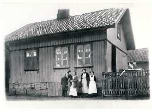 """Med industriutvikling og ny bosetting langs Glomma oppsto behovet for landhandlerier. Bondesønnen Severin Olsen Evje så mulighetene da Evje teglverk kom i drift i 1865. Vareutvalget var mangfoldig. Kjøpmannen kunne levere alt fra parafin til lamper og primus, til kjøkkenutstyr, vaskemidler, tekstiler og alle slags matvarer. Om ønsket vare ikke fantes på lager, kunne den bestilles og leveres innen kort tid. Svært mange kunder handlet """"på bok""""; det vil si at varene ble borget og betalt etter hvert. Daglige forbruksvarer som brød, melk og kjøttvarer, kom med """"Trippen"""" fra Sellebakk og måtte hentes med dragkjerre eller hest og vogn på Evje-brygga. Mel- og sukkersekker, sirups-, grønnsåpe- og sildetønner ble levert med hest og vogn av leverandør i Fredrikstad. Jeg minnes de spesielle luktene. Her kjøpte jeg som 9-åring garn til lusekoftene jeg strikket. På bildet står datteren Anna Ramberg med sønnen Roald på armen. De skulle bli andre og tredje generasjons kjøpmann på Evje."""