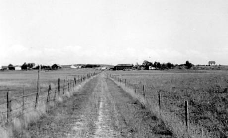 """Gårdsveien fra Rolvsøyveien førte over jernbanelinjen mot gården Saksegård. Veistandarden er representativ for de andre veiene som gikk fra Rolvsøyveien og østover mot bebyggelsen ved Glomma, """"Rågata"""", """"Evjeveien"""" og """"Haugegata"""". Forbindelsen fra Rå til Evje var av eldre dato, mens de andre oppsto som en følge av utbyggingen av hovedveien (FV 109) rundt 1920. Da min familie kom fra Sarpsborg til Rolvsøy en marsdag tidlig på 1930-tallet, kjørte flyttebilen den eldgamle gårdsveien fra Rå til Evje. Det fortelles at jeg gråt og klaget over stygge gater. Fotograf ukjent"""