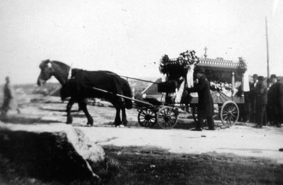 Her er Olivia Jonassen Hjelm på sin siste ferd i likvogn mot Rolvsøy kirkegård i 1929. Rolvsøy hadde ikke kapell på denne tiden, så gravferden foregikk fra hjemmet. Et annet bilde viser gravfølget på vei opp H. N. Hauges vei. Hestene førte an, dernest kjørte et par biler og så fulgte de gående. På denne tiden stoppet trafikken opp i respekt for møtende gravfølger. Kilde: Rolvsøy bygdebok.