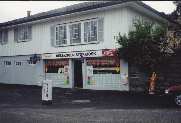 Slik så det ut da Laila Bjørneli var virksom i Rønningveien18 i tiden1.januar 1994 til 31. desember 2002. Diplomismannen ønsker kundene velkommen utenfor butikken. Fotograf ukjent