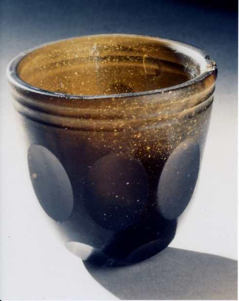"""I 1913 gjorde Laurits Kristensen et spennende funn da han arbeidet i haven på sin eiendom i Rådalsveien 20. Han fant et vakkert romersk glass. Hans datter, Ragna Skaaden, fortalte at glasset ble funnet øst for huset, 5-6 meter fra """"Trestenane"""". """"Rådalsglasset hører hjemme i yngre romersk jernalder (ca 200-400 e. Kr), et tidsrom hvor det romerske imperiet dominerte vår del av verden…."""", skriver Eldrid Straume. Kilde: Rådalsglasset – glemt og gjenfunnet. Erling Johansen og Eldrid Straume. Mindre Alv 1982-82. Årbok for Fredrikstad Museum Foto: Fredrikstad Museum"""