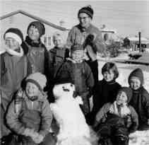 Åpen gård med snemann. Evje 1960-tallet.
