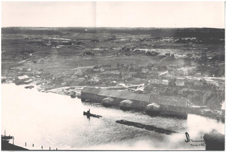 Bildet som er tatt fra pipa på Torp bruk i 1910 viser bordhusene på Hauge med tre husprammer. Til venstre for veien som løper mot Glomma ligger Hauge prambyggeri. Fotografen har også oppfanget en slepebåt med tømmerslep. Repro: Bjørge Mariussen.