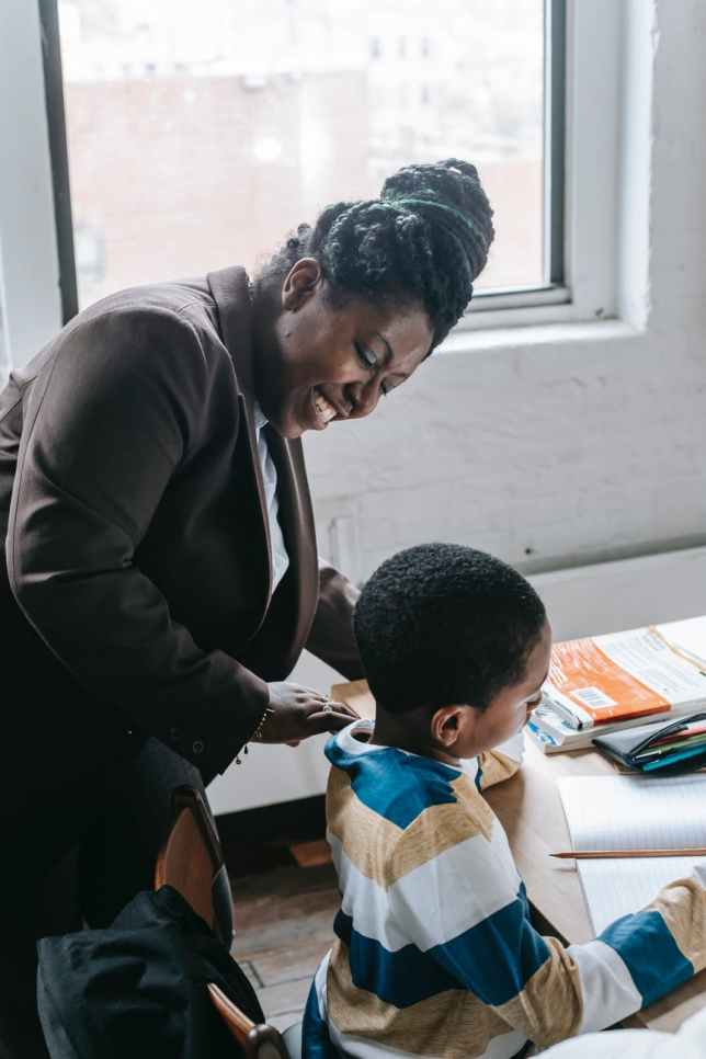 cheerful black female teacher helping pupil with task