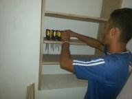 Gabi puts the screwdrivers on the shelf.