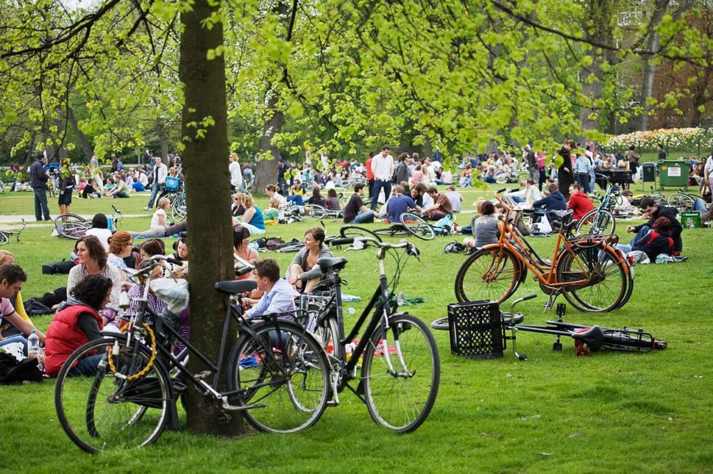 Cyclists and pedestrians having a picnic in Amsterdam park