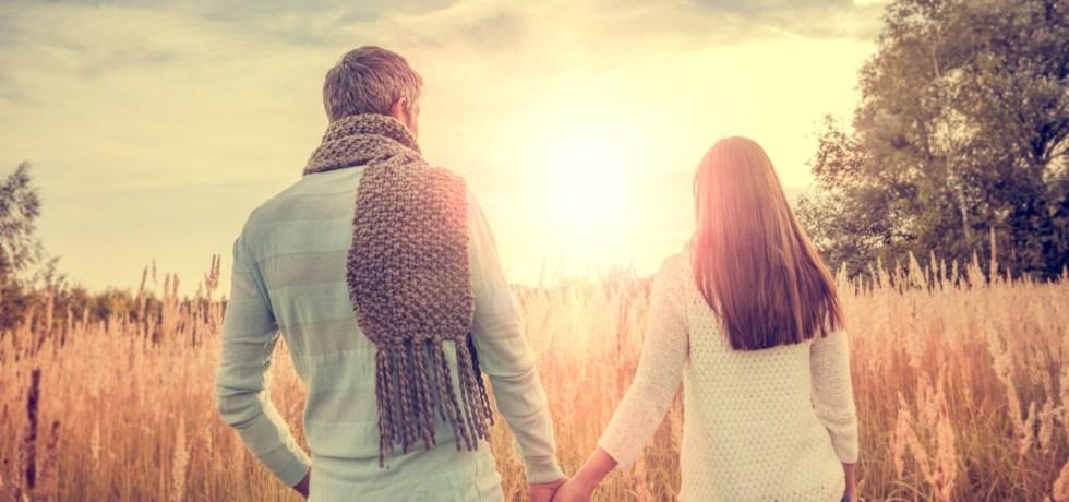 zakochana i szczęśliwa para trzymajaca się za ręce i idąca wspólną drogą