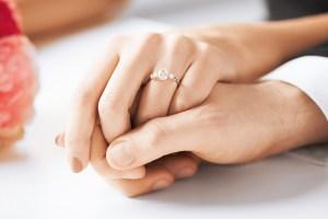 para trzymajaca się za rece, na ręce kobiety widac pierścionek zaręczynowy