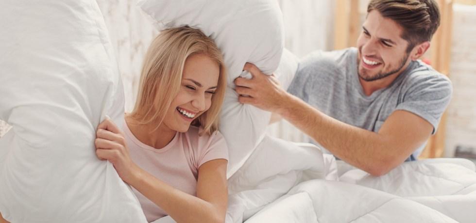 bitwa na poduszki w łóźku dwojga dorosłych ludzi, którzy są przyjaciółmi i kochankami; przyjaźń i zabawa w związku