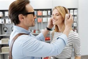 mężczyzna nakładajacy kobiecie słuchawki, aby mogła posłuchac romantycznej muzyki
