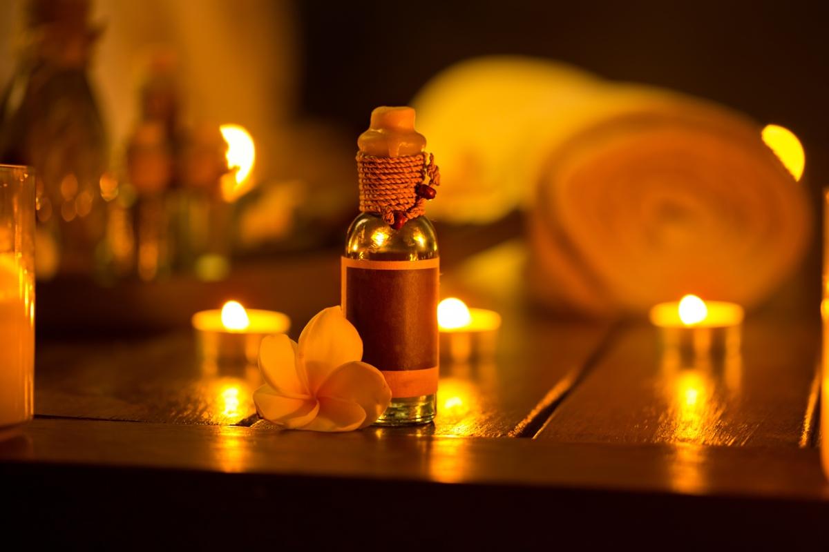 butelka olejku eterycznego na stole z zapalonymi świecami, które tworzą zmysłową atmosferę