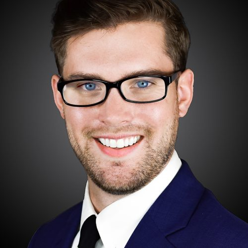 A young man wearing glasses from Queens and Brooklin having his headshot taken