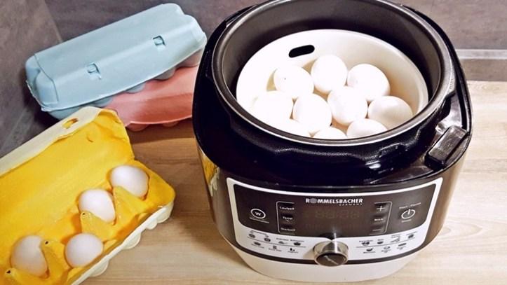 Multikocher mit weißen Eiern und drei bunten Eierkartons. ROMMELSBACHER Dampfdrucktopf als Eierkocher.
