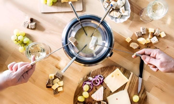 Fondue Set mit Käsefondue, Brotwürfel auf Fonduegabeln und Käse-Trauben-Deko