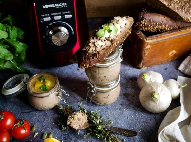 Brotscheibe mit Leberpastete und Deko aus Zwiebel, Tomaten und Salat vor einem roten STandmixer