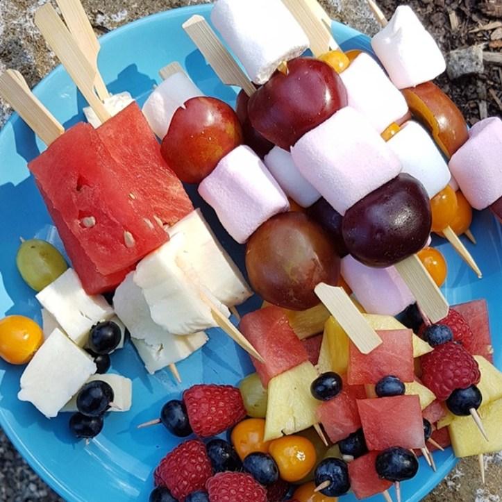 Bunte Girillspieße mit Obst und Marshmallows und Kaese