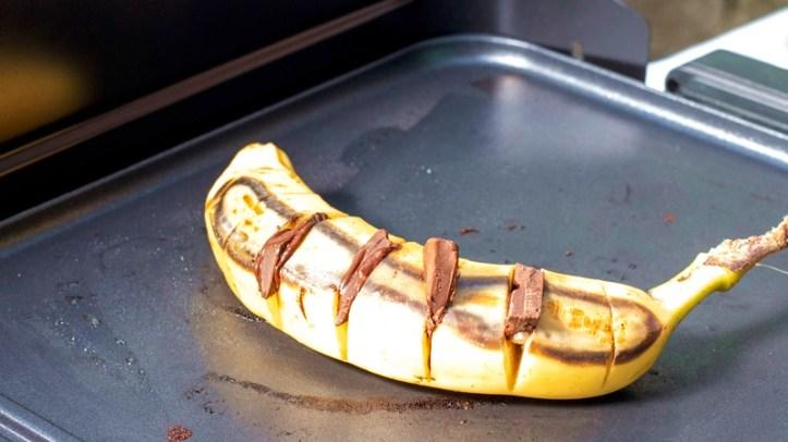 Banane mit Schokostücken gespickt auf dem Tischgrill