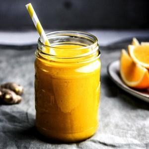 Orangefarbener Smoothie Ingwer-Mango-Orange - im Schhraubglas mit Strohhalm