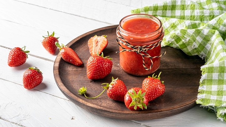 Erdbeer-Kokos-Marmelade in Glas, auf Holzteller mit grün-weissem Tuch und Erdbeeren