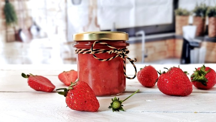 Erdbeer Kokos Marmelade im Glas mit Erdbeeren auf weißem Tisch