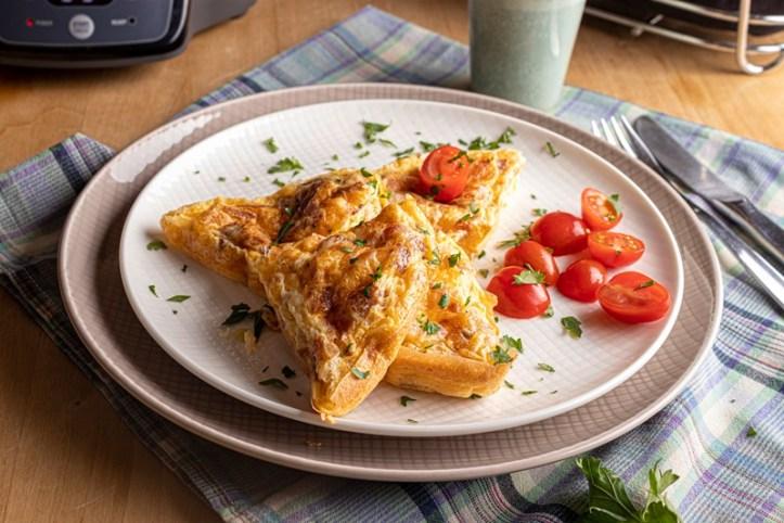 Huetten-Omelett, gebacken im Omelett Chef Oskar OM 950 von Rommelsbacher. Serviert mit Mini-Tomaten.