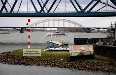 Een schip geladen met hout vaart tegen de wind in op de Waal richting Rotterdam.