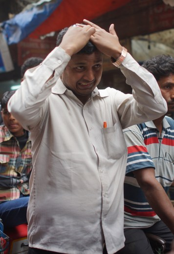 A man combs his hair amid the traffic in Chandni Chowk