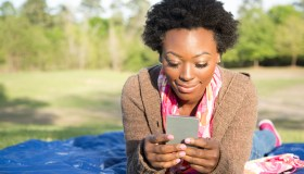 One African descent woman using cell phone outdoors in park.