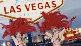 Two Chorus Girls in Full Stage Costume Posing by a Road Sign in Las Vegas