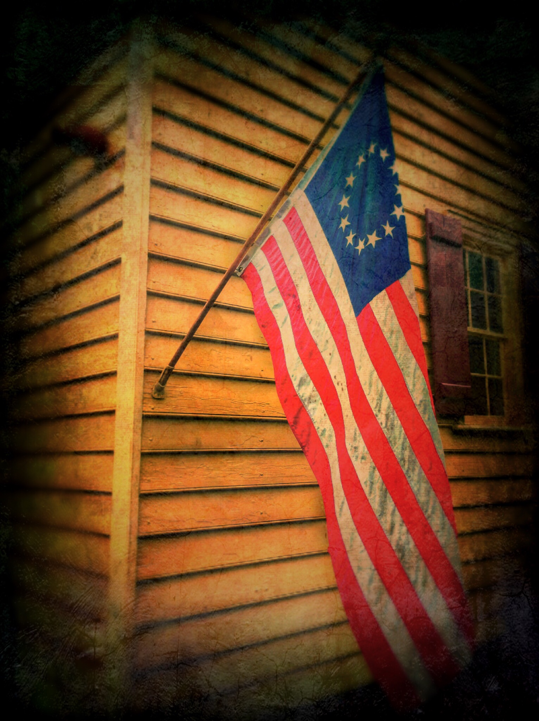 Old American Flag hanging on side of old clapboard building