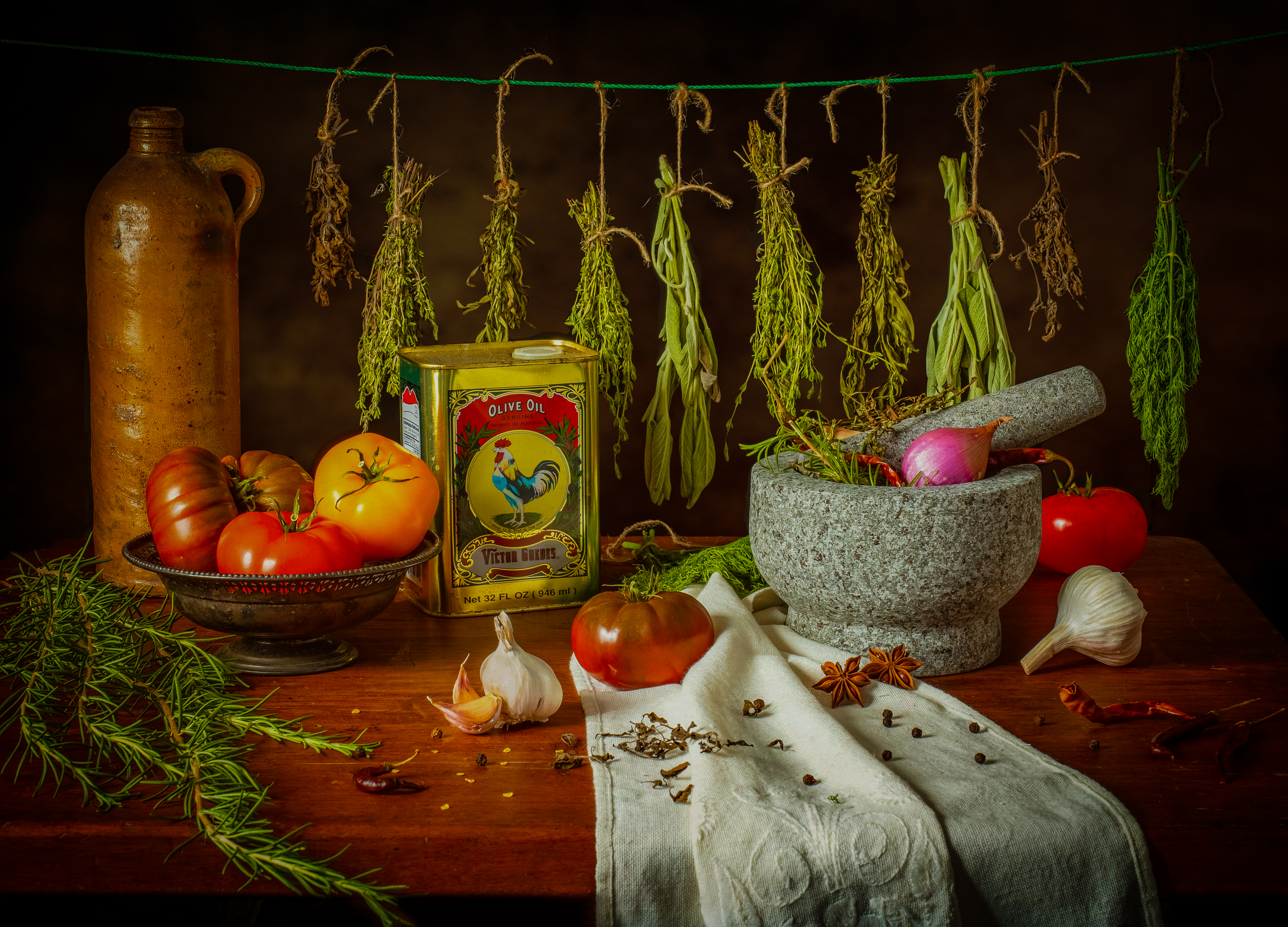 a scene of dried herbs, heirloom tomatoes, onion, garlic, and olive oil with a mortar and pestle