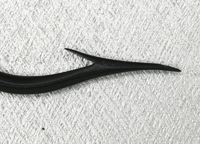 "Eugene Sunday hook, 9/0. Specially made for Al Cohen & was part of Cohen's collection until it was acquired by Paul Rossman. Hook has the ""pouty lip"" Dublin point. From the Reinhold collection.  By looking at this and the other Sunday hooks you can clearly see the relieved taper. That is that the taper is a straight line on top with the shank and the relief is below to allow for the gut to be tied in with minimal bulk.  I have quite a few vintage hooks that clearly predate Sunday's hooks so it can be assumed he noticed it on them and incorporated it on his hooks or he just thought of it on his own. Sunday studied vintage hooks so I tend to believe in the first assumption. In any case, the relieved taper for those attaching the gut below the taper makes the job of keeping bulk to a minimum easier."