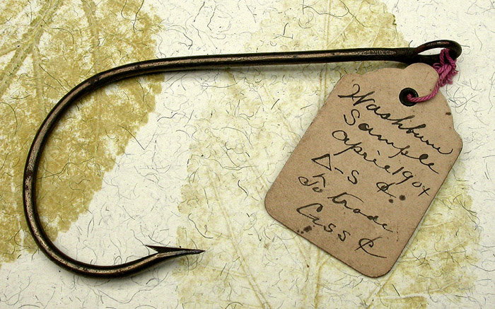 "32a Washburn, sample hook, 13/0, hand formed tapered, welded ring eye, bronzed, ca 1904. The eye on this hook is very big, you could put a ¼"" rope through it. The hand filing is great. You can imagine the hook maker filing the wire to a very fine taper and then bending it, what looks to me to be freehand. I have three of these hooks that are all slightly different. The original tag reads, Washburn, Sample, April 1904, a triangle-S &, to trade, C or G ss and the cents symbol. Were these prototype hooks? I don't recognize the name. There's a story there that we are unlikely to know. 1900's collection."