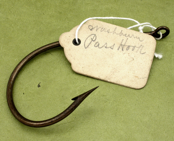 34. The third Washburn, sample hook, 13/0, hand formed tapered, welded ring eye, bronzed, ca 1904. The eye on this hook is also big but smaller than the other two. Once again, the hand filing is great. The original tag reads, Washburn, Pass Hook. The same as the other two except this one is reversed (bent the opposite of kirbed). 1900's collection.