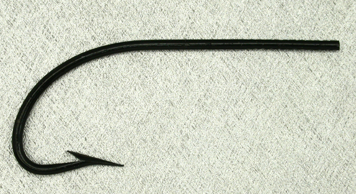 Allcock, limerick, 5.0, japanned. These are two hooks I'm sure from the same box. I can't say what the age of them is but when compared as two of these photos show, they differ significantly. The shanks are different length and the points are as well. It is either hand work or very sloppy machines. I am thinking the latter. Gift from Paul Rossman.