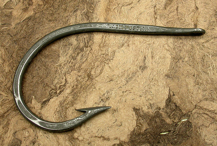 7a E Vom Hofe, Van Vleck hook, about 14/0, tinned, knife edge, needle eye, ca 1910. You can see how thick the plating was back in the day. On some hooks, the stuff just flakes off. On this hook, much of the lettering of the names has been filled in but enough remains to be able to read them. Modern plating technology lays down very thin layers with much better adhesion. Part of the 1900's collection.