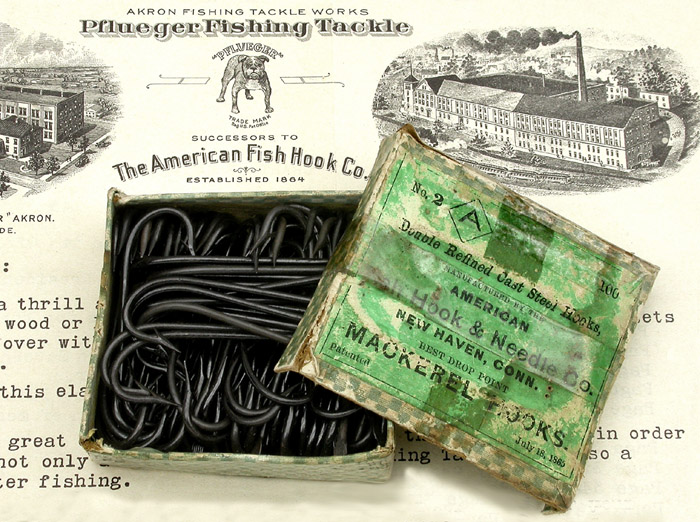 """9c American Fish Hook & Needle Co., #2, Mackerel hooks, drop point, japanned. About 2 1/16"""" long. On the bottom of the box is another label by H.H. Crie & Co., dealers in iron & steel, Blacksmith's stock & tools. Quarry outfits, blasting powder, fuses, &c. Carriage stock, trimmings and paints. Ship chandlery and fishermen's goods. Guns, revolvers, powder, shot &c. Rockland, Me."""